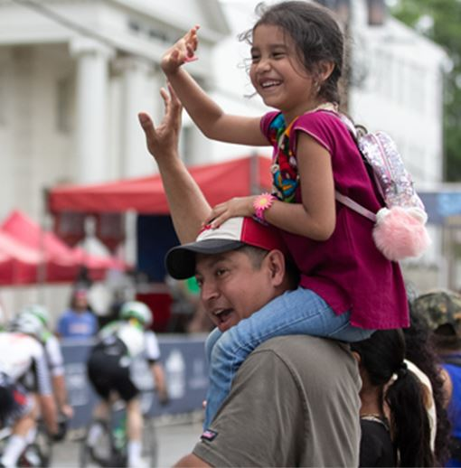 Man and his daughter who sitting on his shoulders waving at the bikers in the bike race